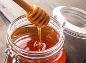 stock photo of dripping  - Honey drip in jar on the table - JPG