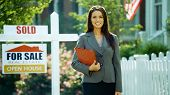 picture of real-estate agent  - A female real estate agents smiles at the camera outside - JPG