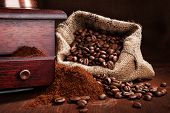 picture of coffee grounds  - Roasted coffee beans in sack with old vintage coffee grinder with ground coffee on wooden background - JPG