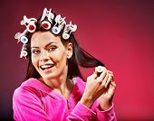 Happy woman wear hair curlers on head.