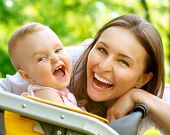 Laughing Mother And Baby outdoors. Nature. Beauty Mum and her Child playing in Park together. Outdoo