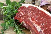 Raw red sirloin steak with fresh herbs, garlic and peppercorns.