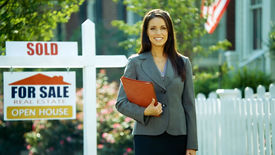 stock photo of real-estate agent  - A female real estate agents smiles at the camera outside - JPG
