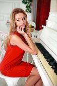 The Attractive Young Woman In A Red Dress Sits On A Chair Near The White Piano, In Home Interior