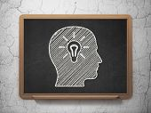 Education concept: Head With Light Bulb on chalkboard background