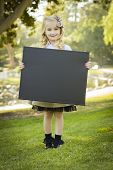 Cute Little Blonde Girl with a Bow in Her Hair Holding a Black Chalkboard Outdoors.