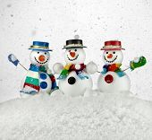 Three Cheerful snowmans in a striped scarfs, mittens and cylindder hat isolated on white background