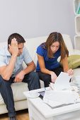 Worried couple sitting on couch and paying their bills in the living room at home