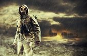 stock photo of lonely  - A lonely hero wearing gas mask city destroyed on the background - JPG