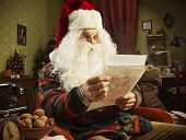 Image of portrait of santa claus reading a letter.