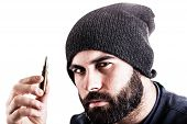 image of extremist  - a bearded man wearing a beanie hat holding a sniper bullet and looking at it - JPG