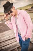 stock photo of take off clothes  - young casual man with hat taking off his sunglasses outdoor portrait - JPG