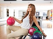 Portrait of beautiful woman with bowling ball sitting on rack in club