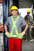 Portrait of happy mid adult foreman with hands on hips and coworker pushing handtruck at warehouse