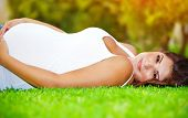 Pregnant arabic woman lying down on fresh green grass field, touching her belly, summer holidays, happy pregnancy concept