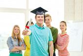 education and people concept - smiling male student with diploma and corner-cap and friends on the back