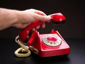 Hand picking up handset of red telephone