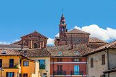 Bell tower of catholic church among typical colorful italian houses in town of La Morra in Piedmont,