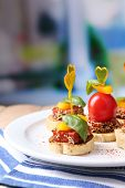 Tasty canapes with salami,tomato, pepper  and basil leaves, on plate, on wooden table, on bright bac