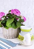 Blooming hydrangea and utensils on table on grey wall background