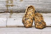 stock photo of baste  - Russian bast shoes on the background of an old village house wall - JPG