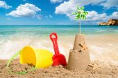 stock photo of spade  - Sandcastle at the beach with bucket and spade - JPG