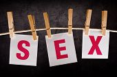 image of intercourse  - Word sex on notes paper hanging on rope attached with clothespins - JPG