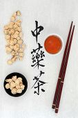 Chinese herbal tea calligraphy script on rice paper with astragalus herb, teacup and chopsticks. Tra