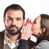 Young Girl Whispering To Her Boyfriend Over White Background