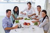 Workers smile at camera while eating healthy lunch in the office