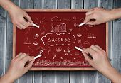 Composite image of multiple hands drawing success doodle with chalk on wooden board