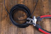 Side cutters cut cable on wooden background