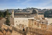 picture of aqsa  - Along the walls of Jerusalem strolls thoughtful woman pilgrim with a backpack - JPG