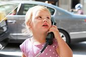 Outdoor Portrait Of Little Girl Talking On The Street Phone