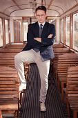 Man Standing In An Old Train Wooden Wagon Or Carriage And Looking At Camera