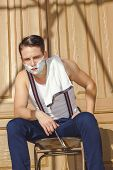 Man With Shaving Foam On His Face And Towel Around His Neck Siting On Chair And  Posing In Front Of