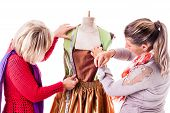 picture of dress mannequin  - two happy seamstresses working on a dress on a mannequin isolated over a white background