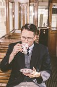 Photo Of Man With Mustache And Glasses On Train Wooden Wagon Drinking Coffee