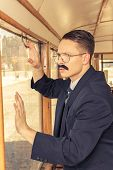 Shocked Man With A Mustache In A Suit With Glasses Posing In An Old Train Wagon