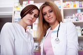 Two Nurses In Front Of Pharmacy Desck Smiling