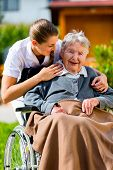 foto of geriatric  - Senior woman in nursing home with nurse in garden sitting in wheelchair  - JPG
