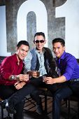 Asian young and handsome group of party people or male friends drinking shots in fancy night club