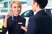 Asian man at car rental receiving key