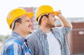 business, building, teamwork and people concept - group of smiling builders in hardhats with clipboard outdoors