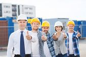 business, building, teamwork, gesture and people concept - group of smiling builders in hardhats showing thumbs up outdoors