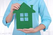 Woman hands holding paper house on light background