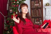 Beautiful adult woman listening music against Christmas tree