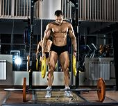 picture of execution  - very brawny guy bodybuilder execute exercise with weight - JPG
