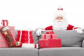 Santa Claus hiding behind a sofa full of Christmas presents isolated against white background