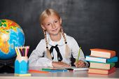 School girl sitting on desk in classroom